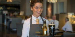 Lounge girl serving Guinness in Dublin Hotel Bar